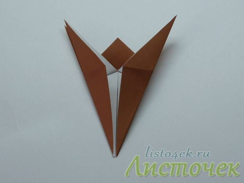 Переворачиваем фигурку на другую сторону и также загибаем боковые треугольники