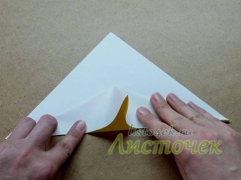 Теперь верхние стороны треугольника с обеих сторон загибаем вниз, используя полученные ранее линии сгибов