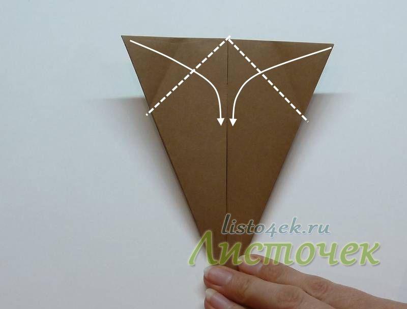 Получаем вот такой треугольник. Правый и левый угол сгибаем к центральной оси