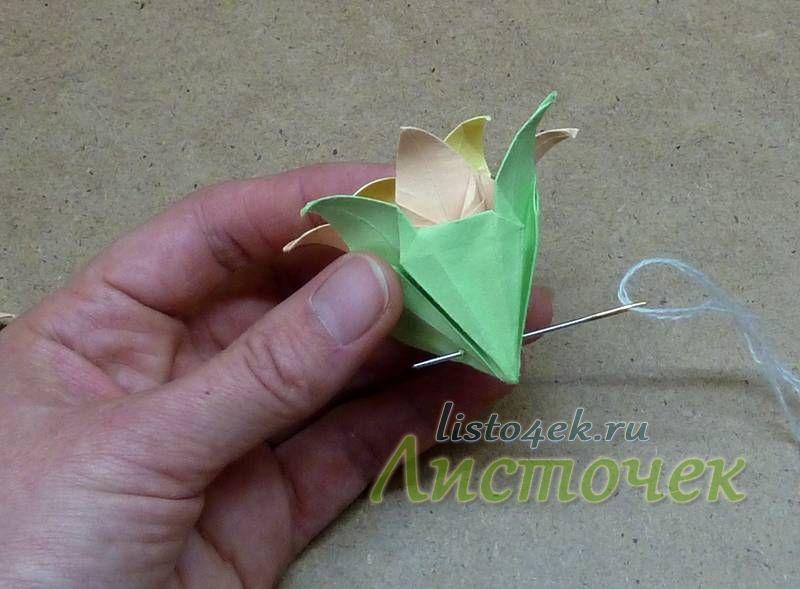 Собранный из трех модулей цветок прокалывается иглой так, чтобы закрепить все три цветка