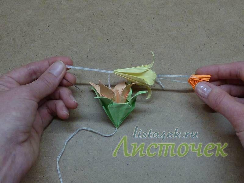 Перебрасываем нитку через линию сгиба серединки и возвращаемся назад, прокалывая верхний цветок, средний и нижний