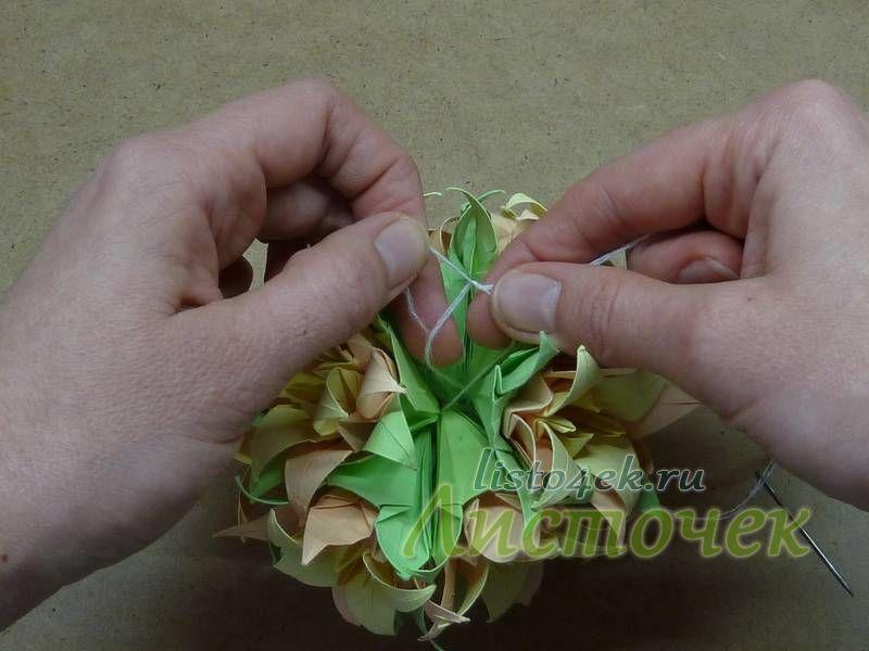 Последний двенадцатый цветок будем крепить по-другому. На нем будет держаться вся кусудама. Поэтому концы нитей можно смело завязывать на узелок