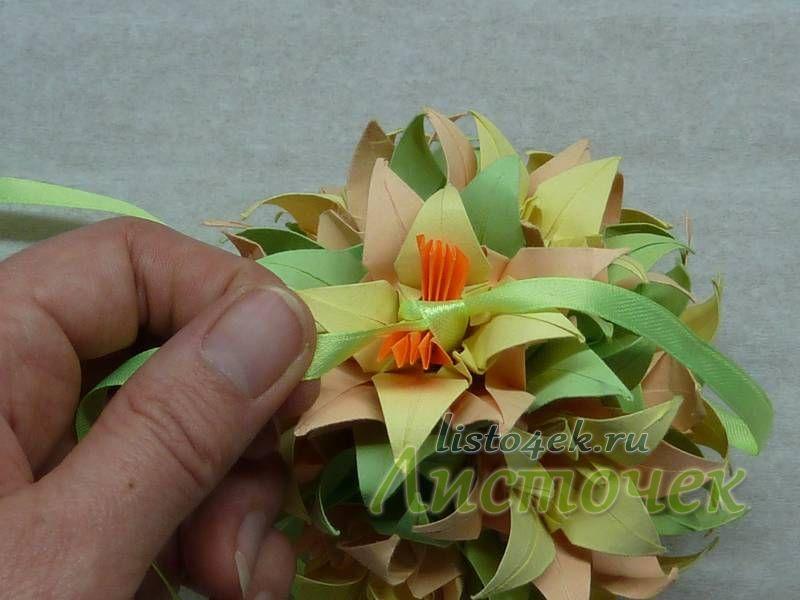 После того как мы протянули ленту через последний цветок, то связываем ее концы над серединкой двойным узлом