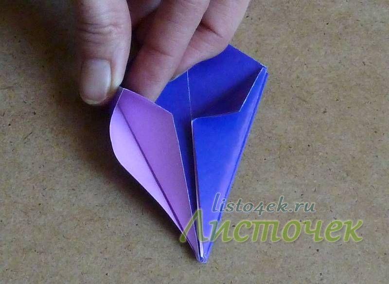 Отгибаем полученный треугольник, надавливая на верхнюю короткую сторону, расплющиваем его по полученным ранее линиям сгиба