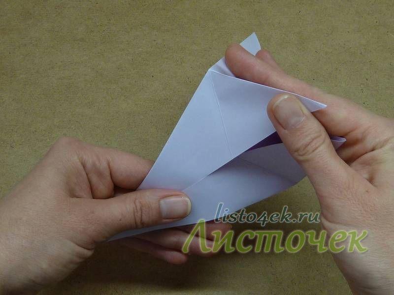 Захватываем эти треугольники одной рукой. Другой рукой совмещаем углы, складывая фигурку пополам
