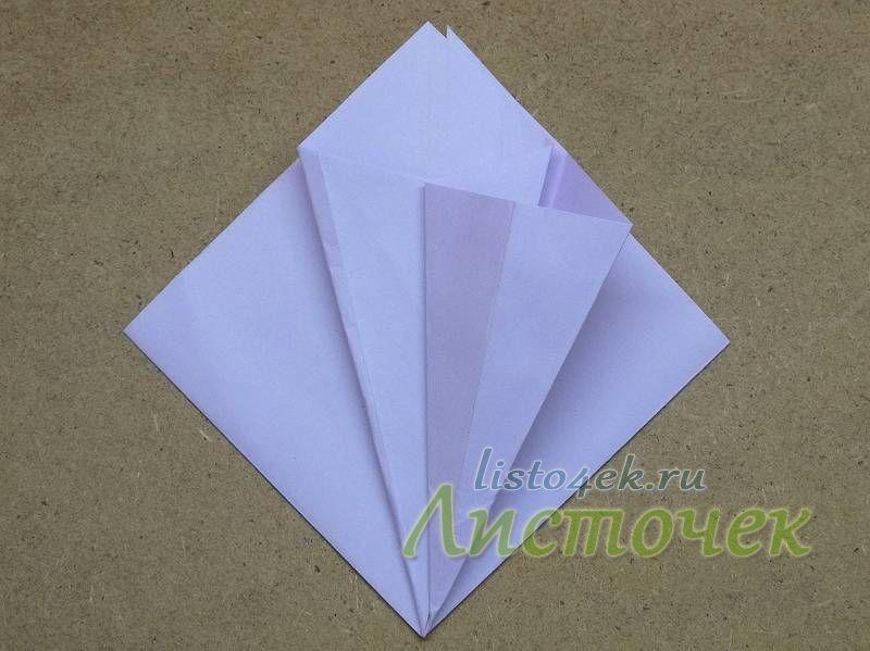 Полученный треугольник отгибаем, и надавливая на верхнюю сторону, расплющиваем его по полученным ранее линиям сгиба