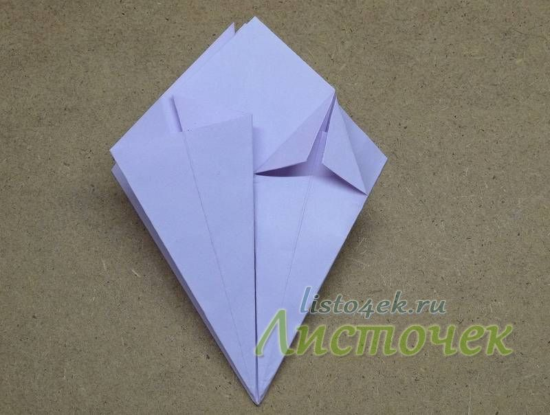 Переворачиваем фигурку на другую сторону и расплющиваем два других треугольника. После этого на расплющенных карманах отгибаем верхние уголки вниз, выравнивая стороны отогнутых треугольников по центральной оси