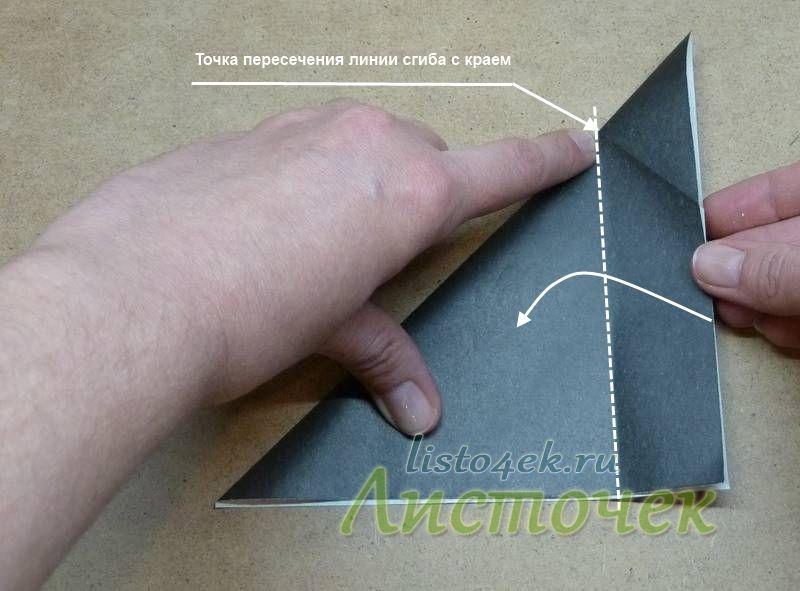 Параллельно краю сгибаем одну из сторон получившегося треугольника, совмещая сторону с точкой пересечения указанной на фото